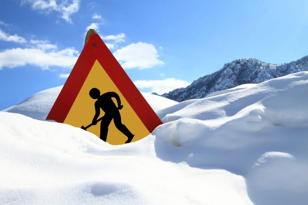 Construction workers caution sign in the snow.